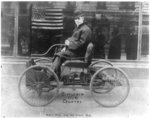 Henry Ford on his first car. [crude U.S. flag superimposed in picture]
